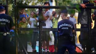 Des officiers de police hongrois montent la garde à la frontière serbo-hongroise, le 15 septembre 2015,  face à des migrants.