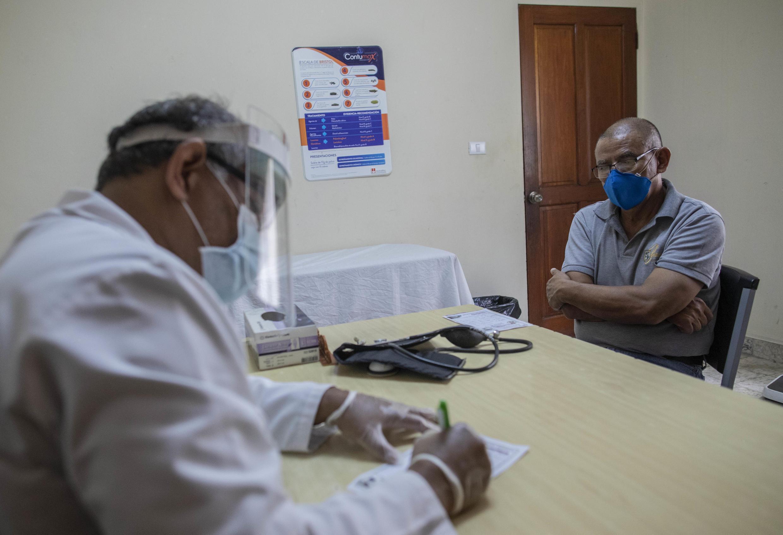 El médico Javier Núñez hace una receta para un paciente en una clínica privada en Managua, Nicaragua, el 3 de junio de 2020, en medio de la pandemia de coronavirus.