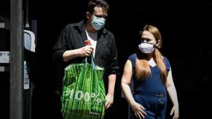 Dos personas salen de una tienda de la ciudad francesa de Burdeos el 18 de julio de 2020