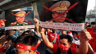 Birmanos que viven en Tailandia sostienen fotografías del comandante en jefe del ejército de Myanmar, el general mayor Min Aung Hlaing, durante una protesta frente a la embajada de Myanmar, en Bangkok, Tailandia, el lunes 1 de febrero de 2021.