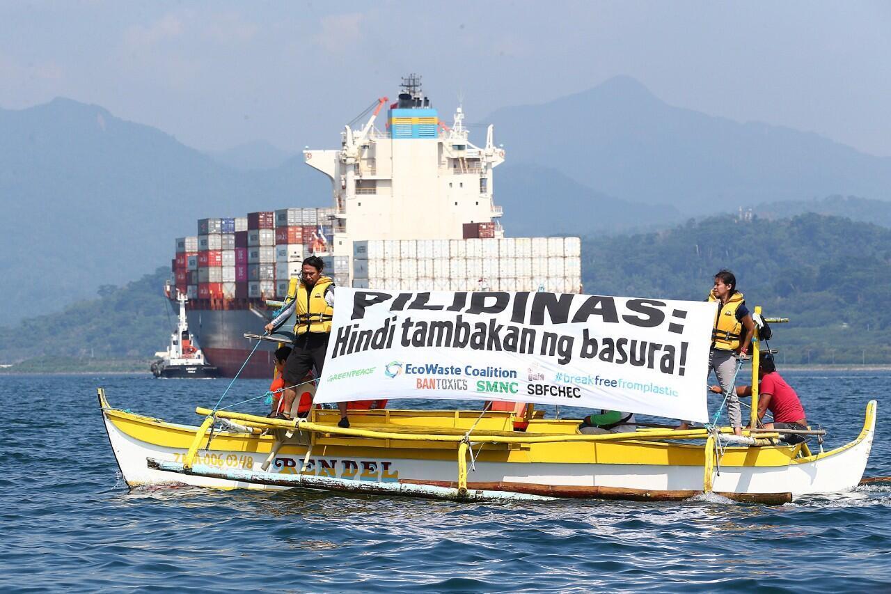 """Varios activistas de Greenpeace mientras mostraban la pancarta """"Filipinas no es un vertedero' delante del carguero MV Bavaria, el buque fletado para devolver contenedores con residuos a Canadá, desde Olongapo, Filipinas, el 30 de mayo de 2019."""