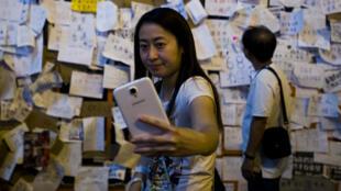Une femme prend un selfie dans le quartier de Mong Kok à Hong Kong, le 30 septembre 2014.