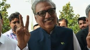 Arif Alvi flashes a victory sign on his arrival before the presidential election at the National Assembly