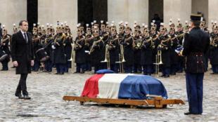 El presidente francés Emmanuel Macron camina hacia el ataúd del teniente coronel Arnaud Beltrame, cubierto con la bandera francesa, en París, Francia, el 28 de marzo de 2018.