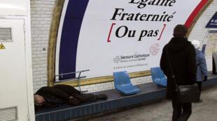Un sans-abri dort dans le métro parisien, en dessous d'une campagne du Secours catholique, pour fuir le froid hivernal.