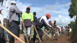 Dans un quartier de Kigali, au Rwanda, les habitants améliorent le système de drainage au bord d'une route.