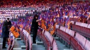 عاملون في ملعب كامب نو يضعون أعلام نادي برشلونة على المقاعد قبل لقائه المرتقب بريال مدريد 6 فبراير/شباط 2019