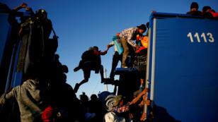 Migrantes intentan ingresar a la parte trasera de un camión en Mexicali, México. 20 de noviembre de 2018.