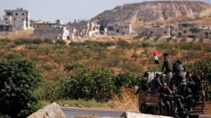 Soldados del ejército sirio viajan en la parte trasera de un camión en la ciudad de Morek, distrito de Hama, Siria , el 24 de agosto de 2019.