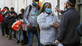 Un trabajador verifica la temperatura de un cliente, afuera de un supermercado en Valparaíso (Chile), que entraba en cuarentena esa misma noche buscando frenar la propagación del nuevo coronavirus, el 12 de junio de 2020.