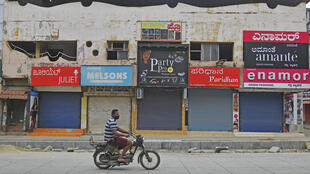 A man in a facemask rides pastshuttered shops in a commercial area  of Bangalore, India's IT hub