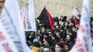 Los manifestantes sostienen pancartas y banderas durante un mitin antirracista en Macerata, el 10 de febrero de 2018.