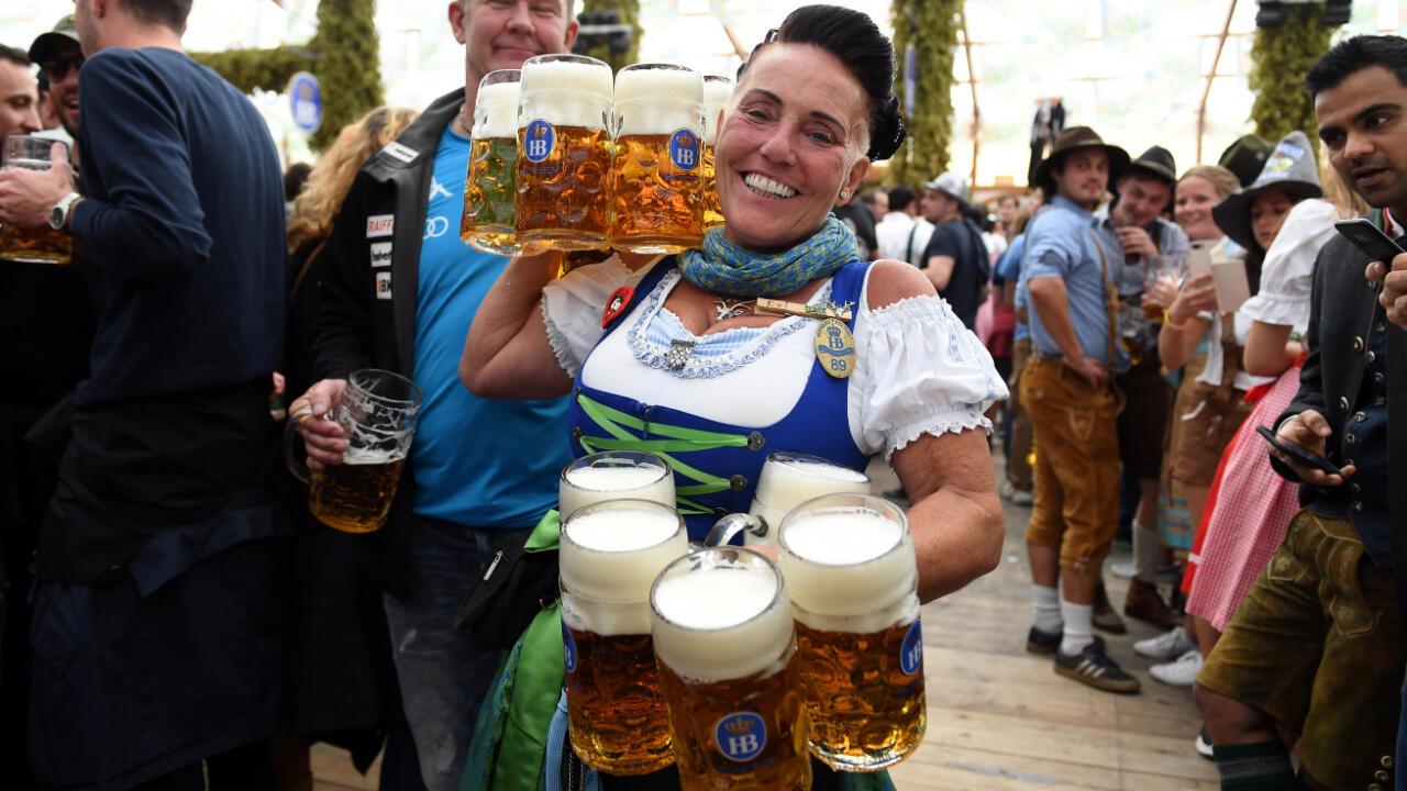 Una mujer sostiene nueve cervezas en el día de apertura de la edición 186 del festival Oktoberfest en Munich, Alemania, el 21 de septiembre de 2019.