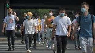Pedestrians wear face masks in Beijing, China. Authorities in the country had appeared to have the virus largely under control
