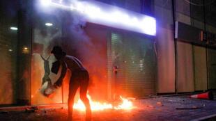 متظاهر يلقي عبوة حارقة على واجهة أحد المصارف في وقت متأخر من ليل 29 نيسان/أبريل 2020 في إطار احتجاجات شهدتها مدن عدة لليوم الثالث على التوالي احتجاجاً على تردي الأوضاع المعيشية