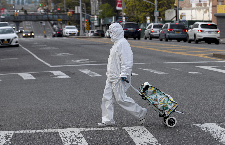 Una mujer vestida con un traje de materiales peligrosos y googles tira su carrito de compras por la ciudad de Nueva York el 20 de abril de 2020