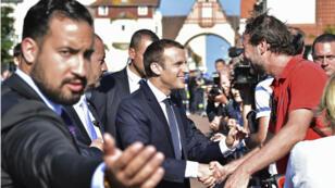 ألكسندر بينالا إلى جانب الرئيس ماكرون خلال زيارته لإحدى المناطق الفرنسية