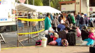 Familias esperan en el Puente Internacional Rumichaca tras entrar en vigor le medida que prohíbe a ciudadanos venezolanos entrar a Ecuador sin un pasaporte válido.