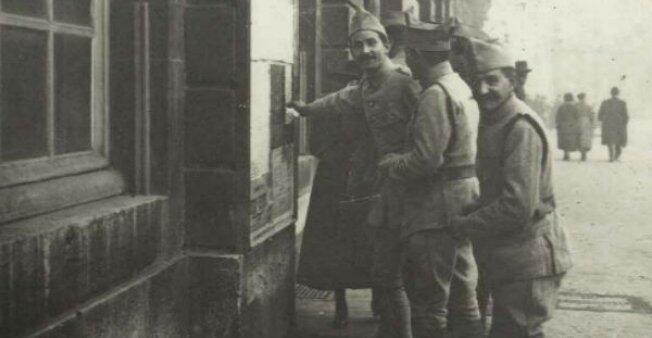 جنود أمام معلقة تعلن نهاية الحرب العالمية الأولى، 11 نوفمبر 1918 في نانسي الساعة 10 صباحا