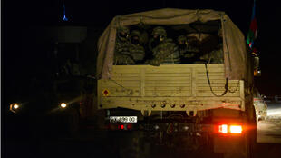 Azerbaijani servicemen ride in the back of a military truck in the town of Lachin early on December 1, 2020.
