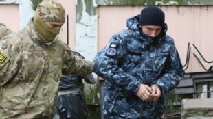 Un agente ruso de la FSB acompaña a un marinero ucraniano a la corte en Simferopol, Crimea, el 27 de noviembre de 2018.