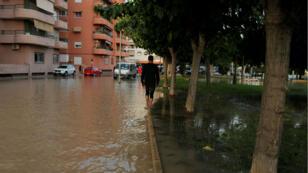 Un homme tente d'éviter l'eau en marchant dans une rue inondée d'Orihuela, en Espagne, le 13septembre2019.