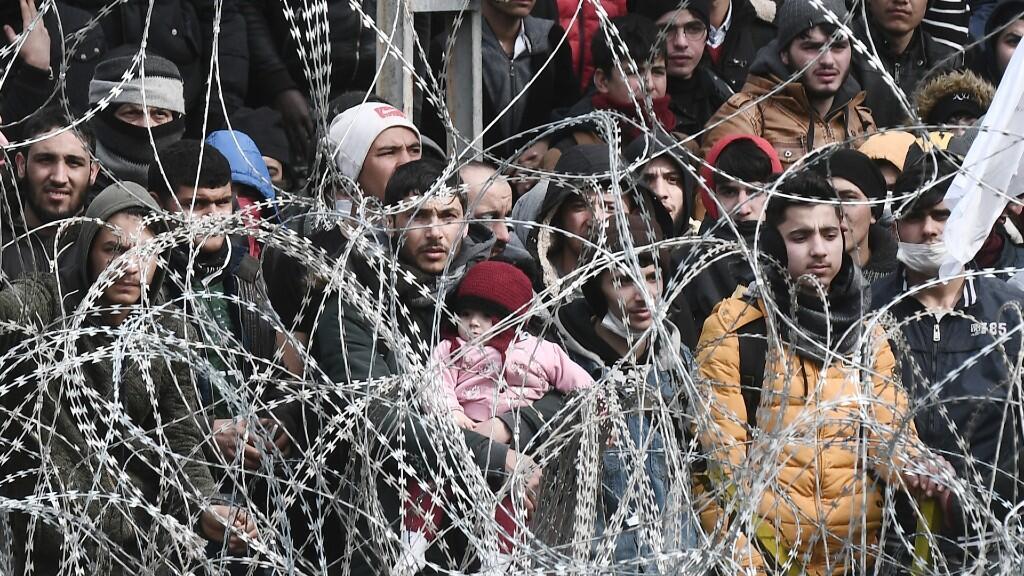 Esta imagen tomada desde el lado griego de la frontera entre Grecia y Turquía, cerca de Kastanies, muestra a los inmigrantes que esperan en el lado turco el 2 de marzo de 2020.