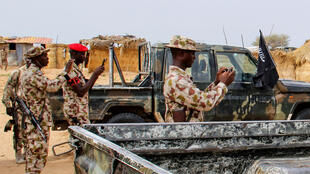 Nigerian soldiers take snapshots of vehicles allegedly belonging to the Islamic State group in West Africa (ISWAP) in Baga on August 2, 2019