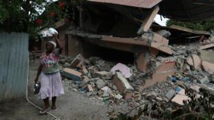 Una mujer pasa junto a una escuela que fue dañada por un terremoto que azotó el norte de Haití el 6 de octubre de 2018.