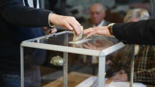 Un électeur dépose son bulletin dans une urne au Touquet, dimanche 7 mai 2017, lors du second tour de l'élection présidentielle.