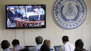 Des journalistes suivent l'annonce du verdict sur des téléviseurs, jeudi 7 août.