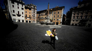 A woman carries her shopping and an Easter egg across Piazza della Rotonda in central Rome, on April 11, 2020 during the country's lockdown aimed at curbing the spread of the COVID-19 infection, caused by the novel coronavirus.