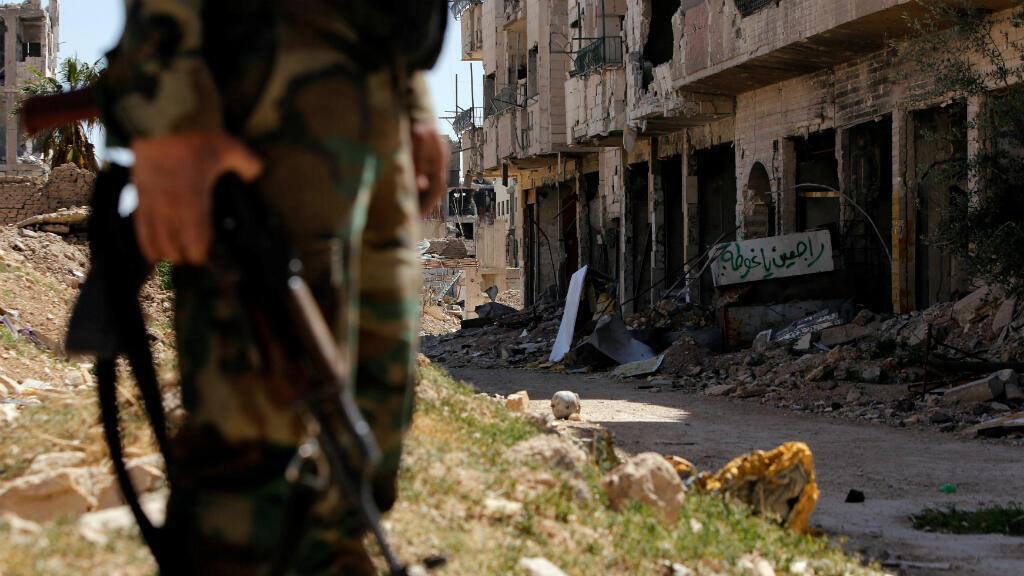 """Un miembro de las fuerzas sirias del presidente Bashar al- Ássad monta guardia mientras un escrito árabe que dice: """"Volveremos, Ghouta"""" se ve en Jobar, el 2 de abril de 2018."""