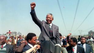 El líder antiapartheid y miembro del Congreso Nacional Africano (ANC) Nelson Mandela levanta un puño al dirigirse el 5 de septiembre de 1990 en Tokoza a una multitud de residentes del campamento de ocupantes del parque Phola durante su recorrido por varios pueblos.