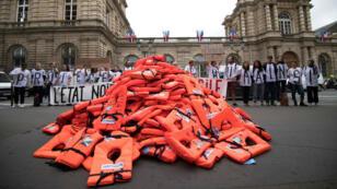 """Des membres du collectif """"Accueil de merde"""" ont installé un tas de gilets de sauvetage devant le Sénat pour manifester contre la politique migratoire du gouvernement français, le 19 juin 2018."""
