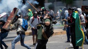 Des manifestants jetant des pierres lors d'affrontements entre partisans et adversaires du président Evo Morales, le 28 octobre 2019, à Cochabamba au sud-est de La Paz.