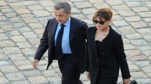 الرئيس الفرنسي السابق نيكولا ساركوزي (يسار) وزوجته المغنية كارلا بروني يصلان لحضور حفل التكريم الوطني للمغني تشارلز أزنافور في باريس، 5 أكتوبر تشرين الأول 2018