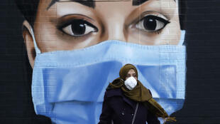 A woman wearing a mask walks past a mural of an NHS health service worker in central London on April 22, 2020.