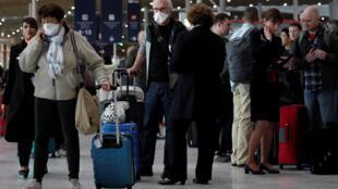 مسافرون يرتدون الكمامات الصحية في مطار شارل ديغول - باريس 12/03/2020