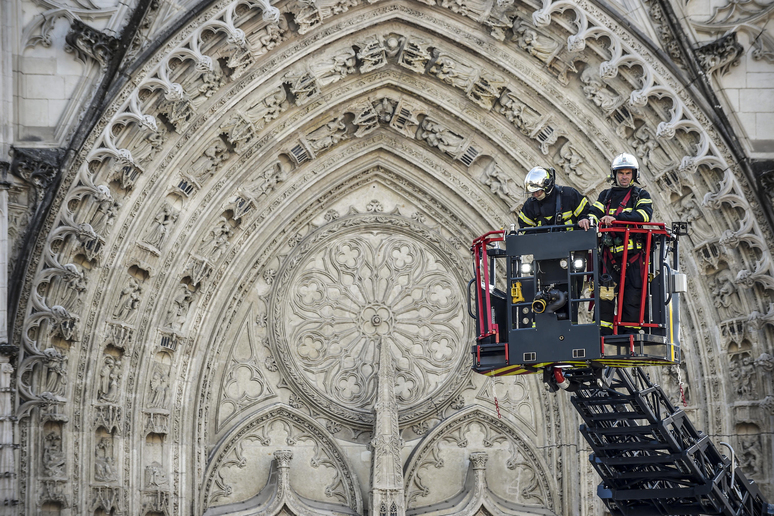 Firefighters climb to inspect the damage to Nantes Cathedral in western France, July 18, 2020.