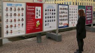 Votantes finlandeses observan los carteles electorales con los candidatos de los partidos en Helsinki en las elecciones parlamentarias del domingo 14 de abril de 2019.