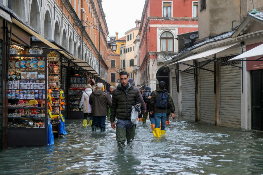People slosh through floodwater in a Venice street on November 15, 2019.