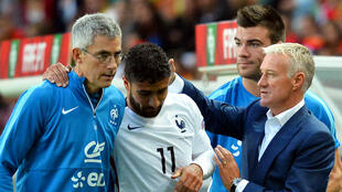 Le Lyonnais Nabil Fekir, entouré du staff de l'équipe de France, juste après sa grave blessure au genou.