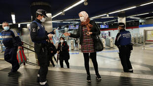 A municipal police officer gives out free protective face masks at a metro station in Madrid, Spain, April 13, 2020.