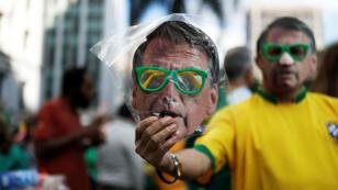 Un vendedor ambulante propone una máscara de Jair Bolsonaro, legislador de extrema derecha y candidato presidencial del Partido Social Liberal (PSL), en una manifestación el 21 de octubre de 2018, en Sao Paulo, Brasil.