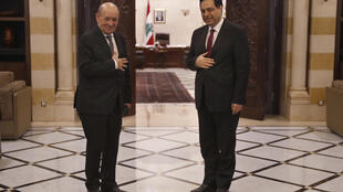 Lebanese Prime Minister Hassan Diab, right, receives French Foreign Minister Jean-Yves Le Drian, as they don't shake hands to help prevent the spread of the coronavirus, at the Government House, in Beirut, Lebanon, Thursday, July 23, 2020.