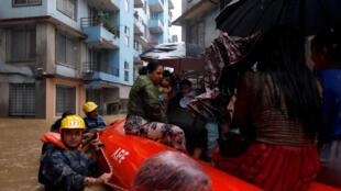 Policía transitando por las calles en botes inflables para ayudar a evacuar a los residentes de las casas inundadas. Katmandú, Nepal, el 12 de julio de 2019.