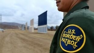 A US Border Patrol officer stands near prototypes of President Donald Trump's proposed wall, in San Diego, California in November 2017