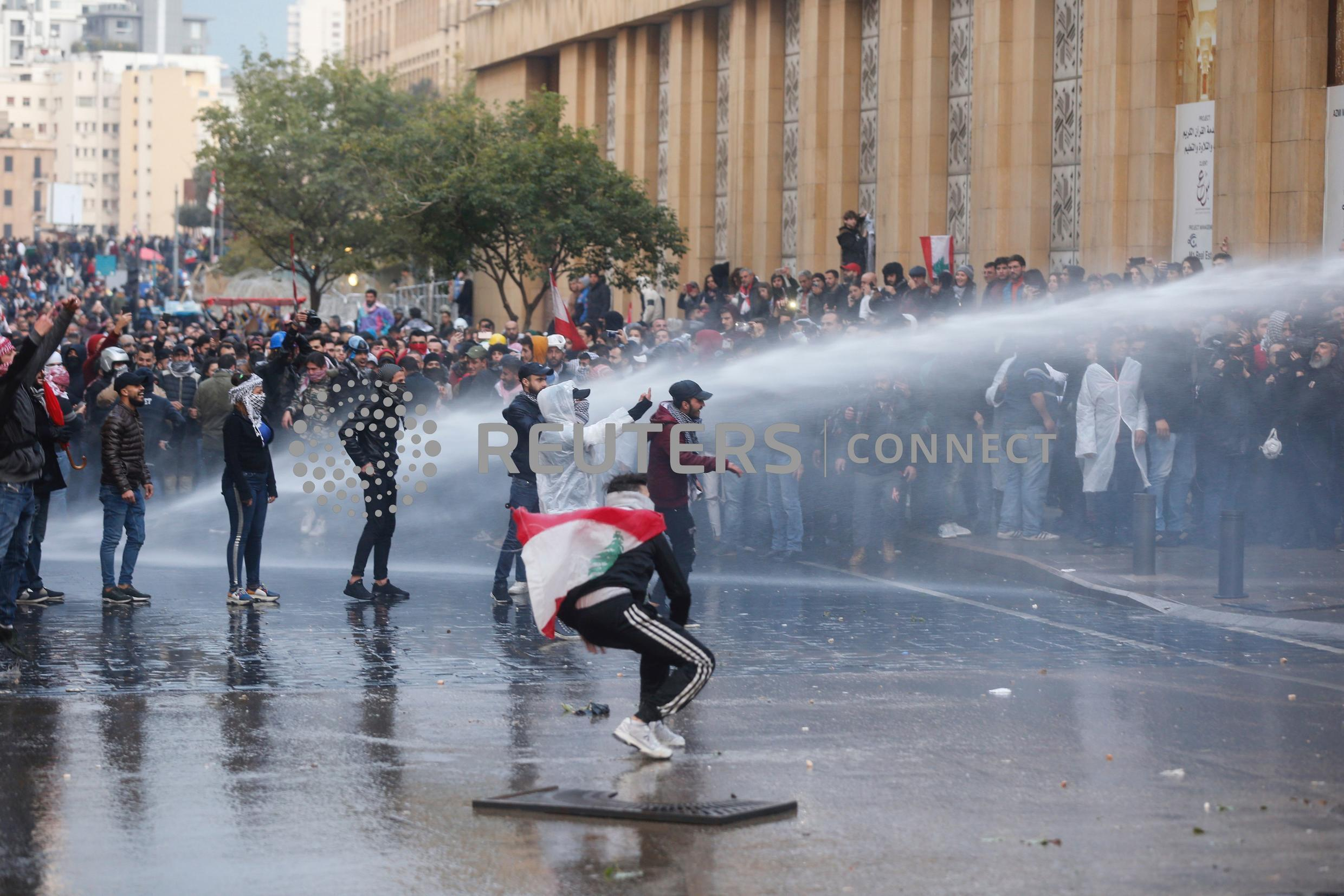 Demonstrators hit by water canon during clashes with riot police in Beirut, January 18, 2020.