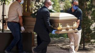 Trabajadores de una empresa fúnebre transportan el cuerpo de Sergio Bretado, un empleado del Hospital General Regional de Ciudad Juárez, México, el 15 de mayo de 2020, víctima del coronavirus